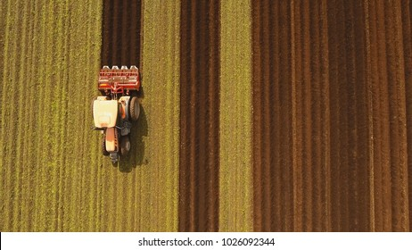 Farmer in tractor preparing land with seedbed cultivator in farmlands. Tractor plows a field. Agricultural work in processing, cultivation of land. Farmers preparing land and fertilizing. Agricultural
