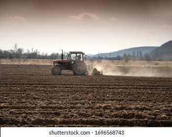 Farmer in tractor preparing land with seedbed cultivator in early spring.  Pre seeding activities of agricultural works at farmlands