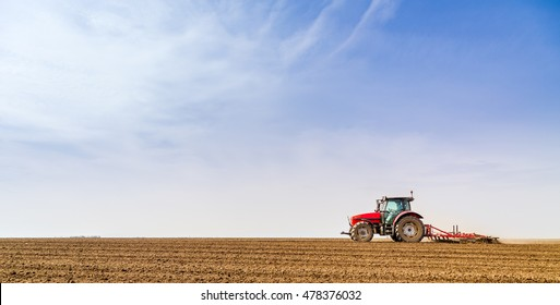 Farmer in tractor preparing land with seedbed cultivator