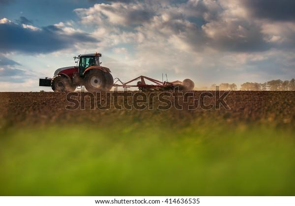 Fermier en tracteur préparant un terrain avec un cultivateur de plantules, tir au soleil couchant
