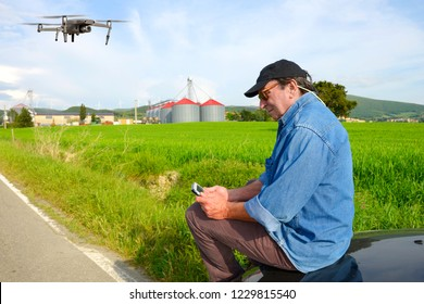 Farmer using drone with tablet in a wheat field with silos