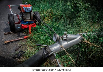 Farmer using pumping water (motor engine) for pump water out of the paddy fields after heavy rains in the rainy season in Thailand