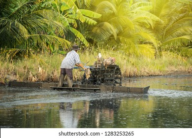 Farmer using tiller tractor plowing in rice field. landscape surrounding area is filled with coconut trees and banana trees. Lifestyle agriculturist countryside of Thailand.