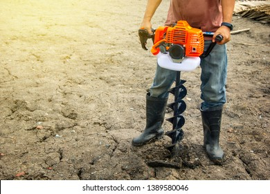 farmer using tools hand-held soil hole drilling machine or portable manual earth auger for prepare the soil for planting trees with soil mold background organic farming and copy space.