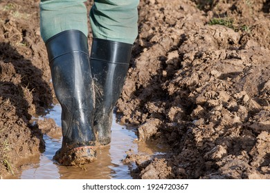 A farmer walks through a moat next to the plowed field in his muddy rubber boots.