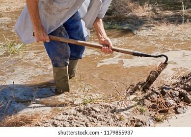 Farmer watering fields wearing wellies and using a spade.