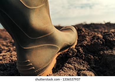 Farmer in wellington rubber boots making first step in field, close up. Beginning of agricultural season and starting of activities on farmland.