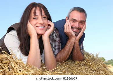 Farmer and wife laying in hay