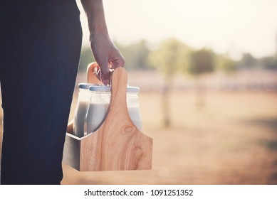 Farmer woman holding bottle of fresh milk on the farm in the summer