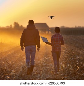 Farmer woman with laptop and landowner walking on field with drone flying above farmland at sunset