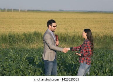 Farmer woman shaking hands with businessman with folder, in corn field