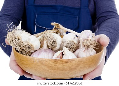 Farmer with a wooden bowl with garlic in his hands