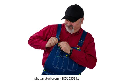 Farmer or worker fiddling with the fastener on his bib overalls as he attempts to dress or undress isolated on white