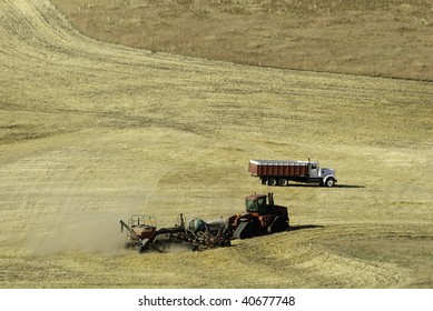Farmer working the field with tractor. He is tilling and spraying the field in one go around.