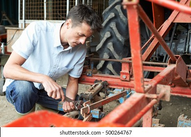 Farmer Working On Agricultural Equipment In Barn