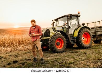 Bauern, die in der modernen Landwirtschaft mit Smartphone arbeiten - Traktorhintergrund