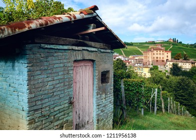 Farmer's abandoned toolshed and vineyards in the village of Barolo (Piedmont, Italy) with the town and the medieval castle on background. Barolo is the main village of the Langhe wine district