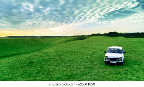 Farmer's car and green field against the sky. Russian rural landscape