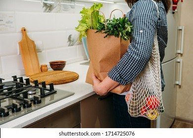 Farmers Cheap food delivery. Direct delivery from farms, buy local, support small food business. Woman unpacks shopping bag with fresh organic vegetable products in the kitchen at home