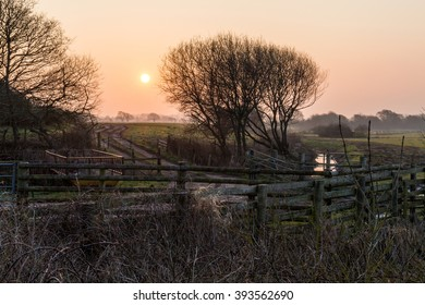 farmers field view with winter sunrise and mist