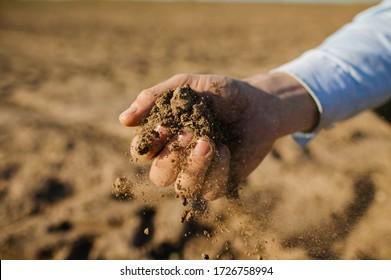 Farmer's Hands Hold A Handful Of Fertile Land, Close-Up