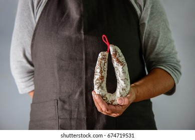 Farmer's hands are holding an artisan aged salami