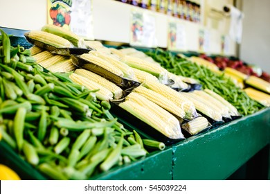 A farmer's market display of fresh produce like corn, okra and red potatoes in green wooden shelf.