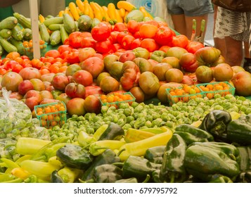 Farmer's market produce for sale at stand. Color horizontal photo of heirloom tomatoes, cherry tomatoes, brussels sprouts, zucchini, squashes, gypsy peppers and bell peppers are visible.