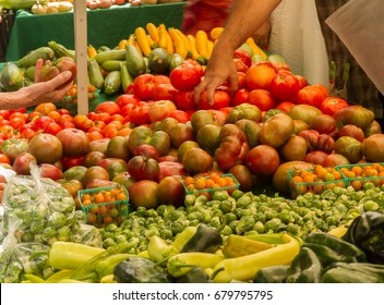 Farmer's market produce for sale at stand. Color, horizontal photo of heirloom tomatoes, peppers, brussels sprouts, squash. Woman's hand on left holding a tomato, man reaching for tomatoes on right.