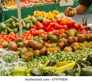 Farmer's market produce for sale at stand, with person holding an heirloom tomato. Cherry tomatoes, brussels sprouts, zucchini, squashes, gypsy peppers and bell peppers are visible.