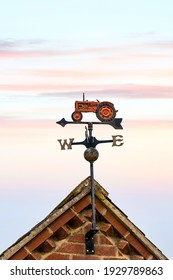 Farmers weathervane metal red old tractor on barn rooftop showing north east south west wind direction with arrow pointer in front of sunset sky