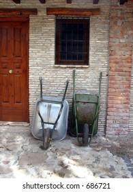 Farmer's wheelbarrows lying on a farm house wall