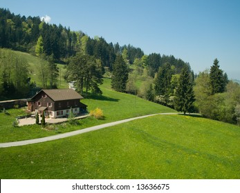 Farmhouse in green alpine meadow, Switzerland