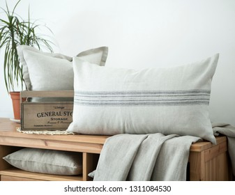 Farmhouse style linen pillows composition on wooden bench. Country style cushions.