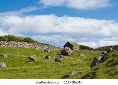 Farmhouse in Torshavn, Denmark. Old stone house in farm yard on cloudy blue sky. Typical rural architecture. Nature and environment. Beautiful landscape view. Summer vacation in country.