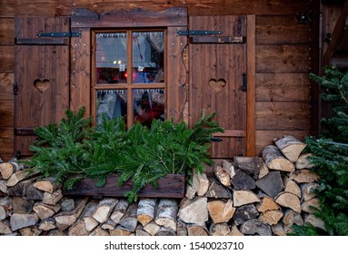 Farmhouse window with aged wood shutters and green conifer tree branches above stack of firewood. Rustic wooden decorations at Christmas fair in Berlin Germany. Authentic Christmas village.