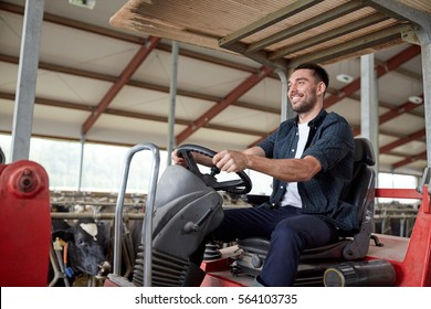 farming, agriculture and people concept - happy young man or farmer driving tractor at farm