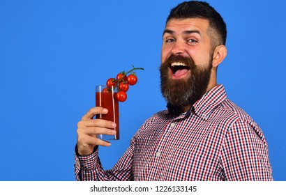Farming and autumn concept. Guy holds homegrown harvest. Farmer with cheerful face offers fresh juice with bunch of cherry tomatoes. Man with beard holds glass of tomato juice on blue background