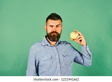 Farming and autumn products concept. Farmer with confused face holds fresh apple. Guy presents homegrown harvest. Man with beard holds green fruit isolated on green background