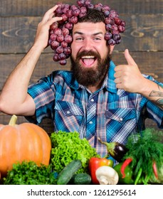 Farming concept. Farmer proud of grapes harvest. Man hold grapes wooden background. Farmer bearded guy with homegrown harvest grapes put on head. Fresh organic harvest. Grapes from own garden.