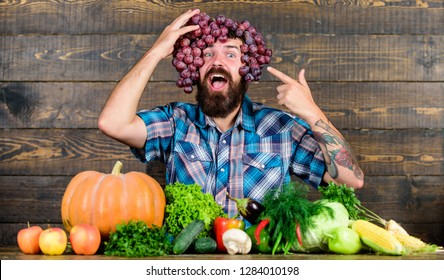 Farming concept. Man hold grapes wooden background. Farmer bearded guy with homegrown harvest grapes put on head. Farmer proud of grapes harvest. Fresh organic harvest. Grapes from own garden.