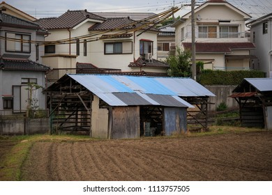 Farming shack in Japanese neighborhood with field prepared for planting
