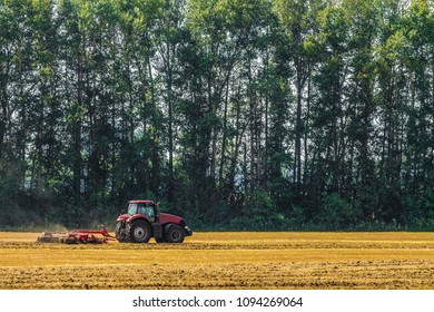 Farming tractor is working in the field. Agricultural machinery.