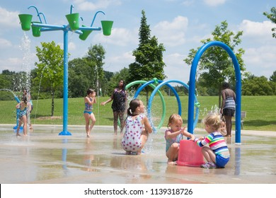 Farmington, Michigan / USA - July 19, 2018: Children of all ages enjoy playing at the Heritage Park splash pad on an 80 degree summer day.