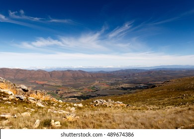Farmland on a plato with mountains in the background looking over the beautiful Swartberg with clouds.