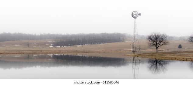 Farmland and pond shrouded in fog on an early spring morning