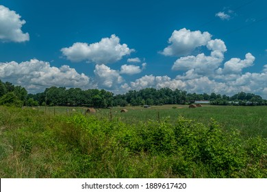 Farmland with rolled hay bales scattered in the field with out buildings clouds and woodlands in the distance on a sunny day in summertime