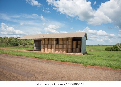 Farmland shelter with stacks of hay by a country roadside on a sunny day in Middle Point, Australia