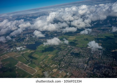 Farms in Holland, Netherlands with canal viewed from plane in sky with clouds, green fields