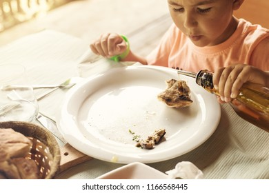 farm-style country lunch, traditional Albanian food. Child pouring olive oil on piece of bread